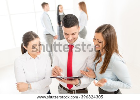 Three smiling young colleagues discussing in front their business team.