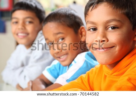 Three smiling young primary school boys sitting in class