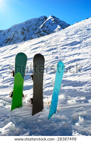 Three snowboards under sun with mountains behind - stock photo