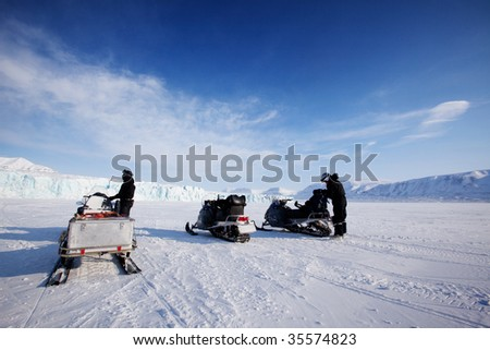 Three snowmobiles in front of a glacier, Svalbard, Norway