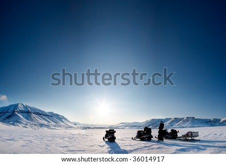 Three snowmobiles on a beautiful winter landscape
