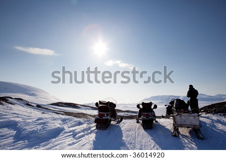 Three snowmobiles on a Svalbard Landscape - winter adventure