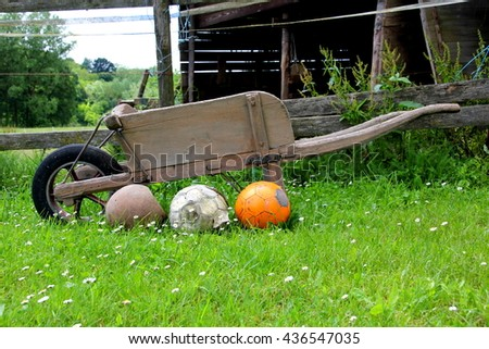 Three soccer balls in front of an old wooden wheelbarrow
