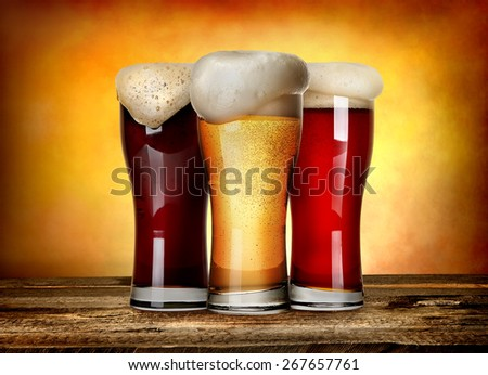 Three sorts of beer on a wooden table - stock photo