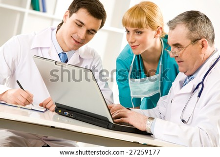 Three specialists looking at laptop screen while elderly man typing document - stock photo