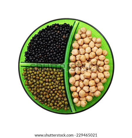 Three species of legumes: chick-pea, mung bean and black lentils on a platter. Isolated on white background. - stock photo