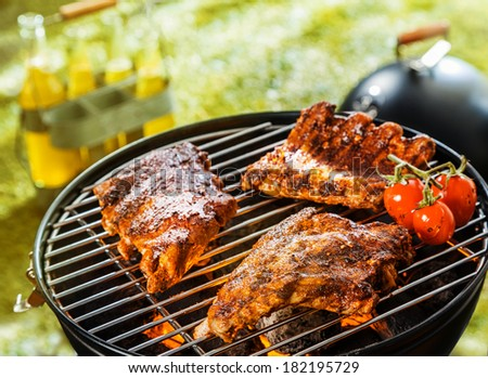 Three spicy racks of rib with cherry tomatoes cooking on a BBQ fire at an outdoor picnic or campsite on a hot summer day - stock photo