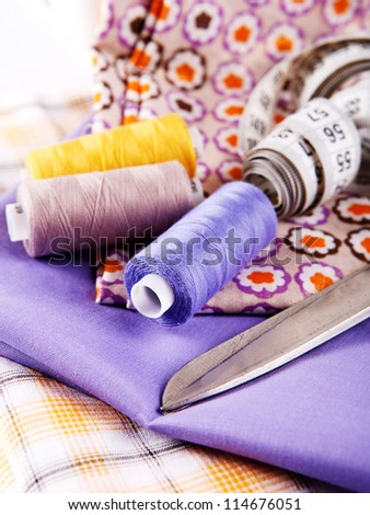 Three spool of colored thread  on pieces of fabric - stock photo