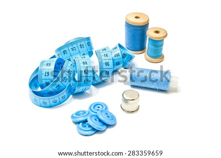 three spools of thread, buttons and meter on white - stock photo