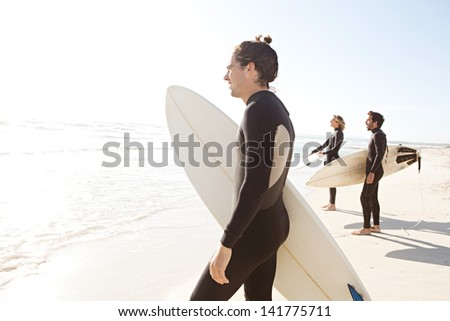 Three sport surfer friends standing together on a white sand beach carrying their surfing boards near the shore during a sunny golden day on vacation, looking out at sea. - stock photo