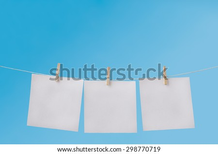 Three squares of note paper for messages, pegged to hang on washing line against a blue sky.  Left blank to provide copy space for notices. - stock photo