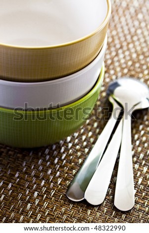 Three Stacked Colorful Bowls On Placemat With Spoons - stock photo