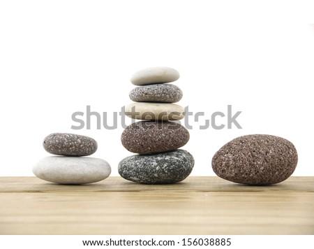 Three stacked stones on a wood board - stock photo