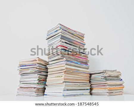 Three stacks of magazines against a white background. - stock photo