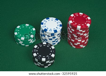 Three stacks of poker chips on a green felt table