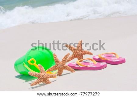 three starfish on beach by toys - stock photo