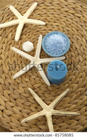 Three starshell and bowl of bath salt and candle on woven wicker mat - stock photo