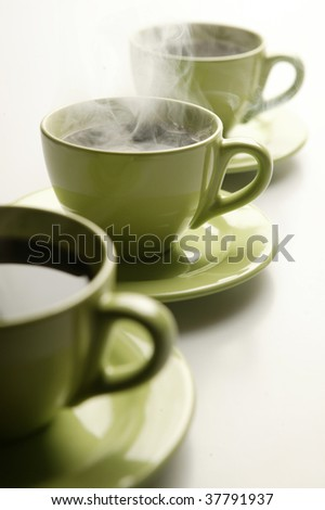 Three steaming mugs in a row in green colors - stock photo