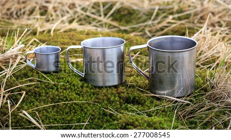 three steel cups on grass