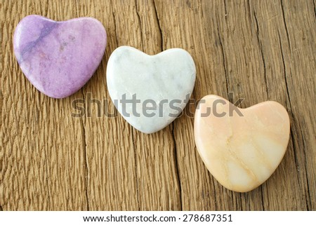 Three stone hearts on rustic wooden board - stock photo