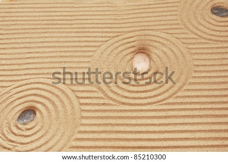 three  stones on a sand background