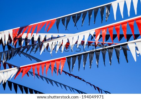 Three strands of festive red, white and black triangular plastic flags (bunting) against a dark blue cloudless sky - stock photo