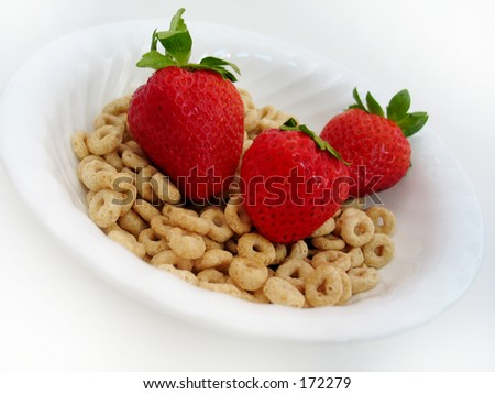 Three strawberries in a bowl of cereal o's in a white bowl. High key. - stock photo