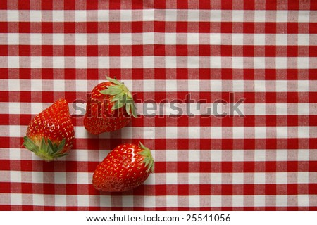 three strawberries on a red and white checkered tablecloth