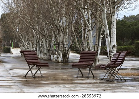 Three street chairs wet in a rainy day in Barcelona Spain