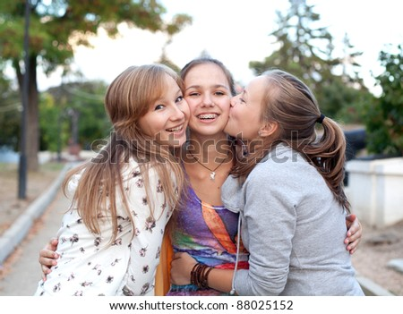 Three student girls having fun in the park - stock photo