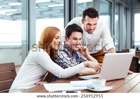 Three students  browsing holiday photos on a laptop - stock photo