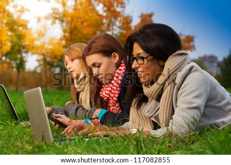 three students browsing in autumn park - stock photo