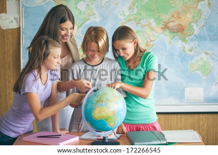 Three students examining a globe with their teacher in a geography lesson. - stock photo