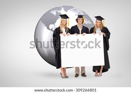 Three students in graduate robe holding a blank sign against grey vignette - stock photo