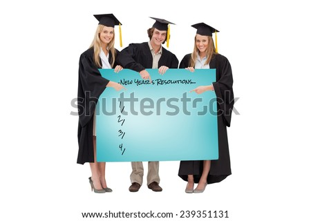 Three students in graduate robe holding and pointing a blank sign against blue card - stock photo