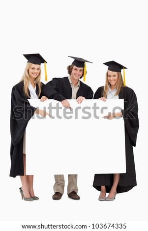 Three students in graduate robe holding and pointing a blank sign against white background - stock photo