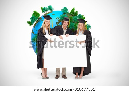 Three students in graduate robe holding and pointing a blank sign against white background with vignette - stock photo