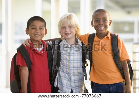 Three students outside school standing together smiling (selective focus) - stock photo