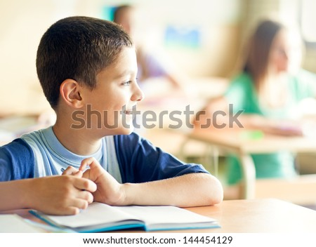 Three students sitting in their classroom. - stock photo