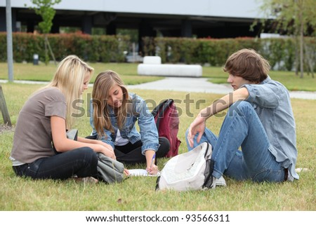 Three students studying on the grass - stock photo