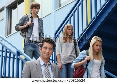 Three students walking down stairs alongside teacher - stock photo