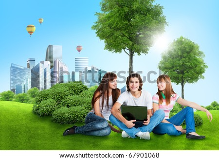 three students with laptop on green grass in the city park