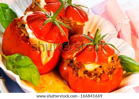 Three stuffed tomatoes on a white plate
