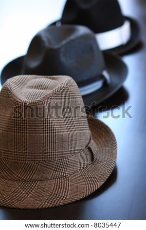 Three stylish dress hats on a table.