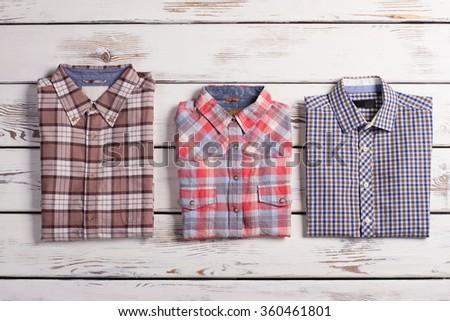 Three stylish men's checkered shirts lying on the white wooden background. - stock photo
