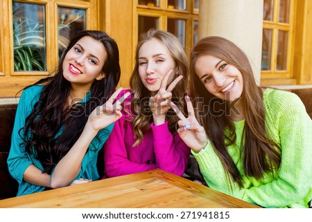 Three stylish pretty girls sitting in cafe   and hugging .  Group of friend enjoying  their time out. - stock photo
