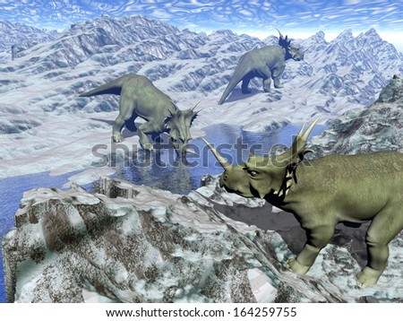 Three styracosaurus dinosaurs in icy desert landscape with water by blue day - stock photo