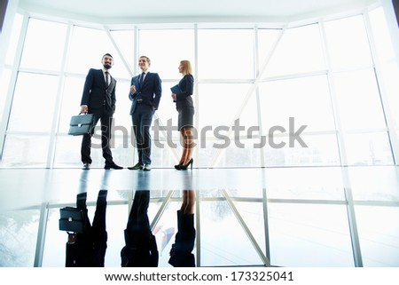 Three successful business partners standing against window in office building - stock photo