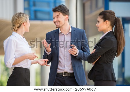 Three successful business people in suits discussing project outdoors. Office background.