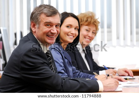 Three successful business team working in the office - stock photo